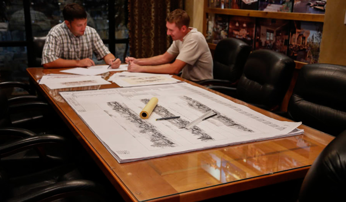 Two men reviewing building construction plans at a big table