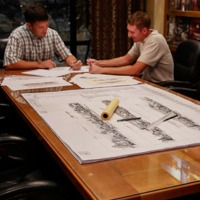 Two men sitting at a conference table reviewing building plans.