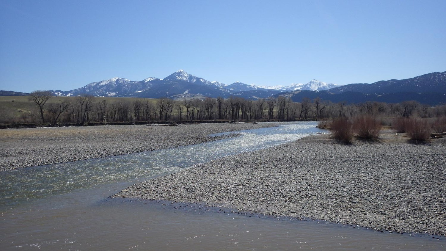 Yellowstone River flowing through rocky banks with mountains in the background