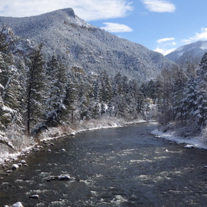 The Gallatin River flowing through snowy evergreen trees, with Storm Castle and Garnet mountains in the background.