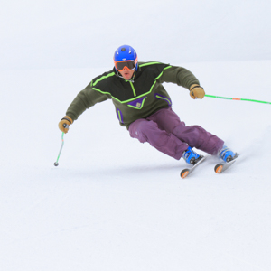 Male downhill skier wearing purple pants and a blue helmet skiing down a groomed slope
