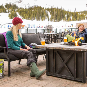 Three friends sitting around on an outdoor patio at a ski resort.