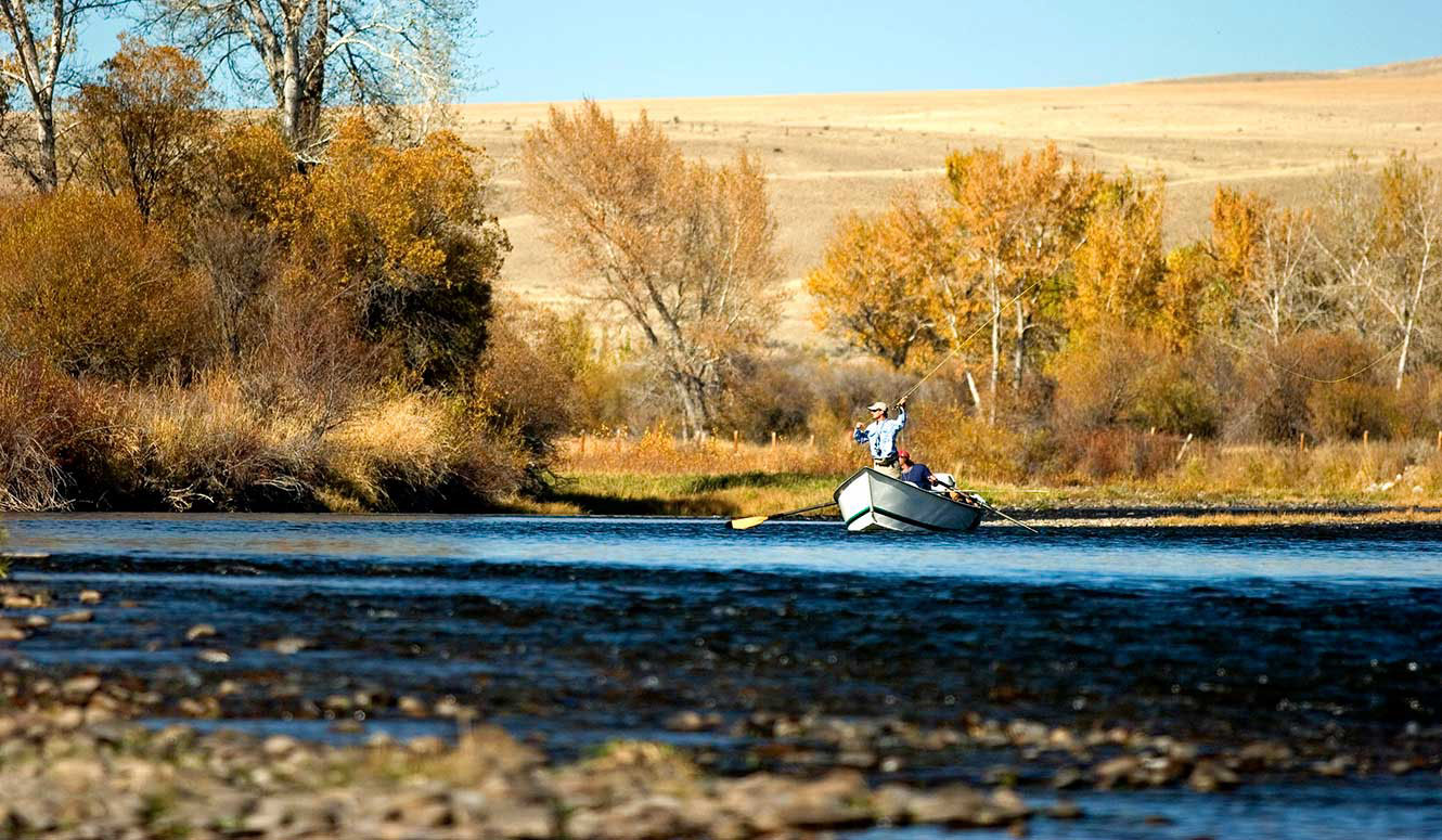 A man fly fishing from a drift boat on a sunny autumn day