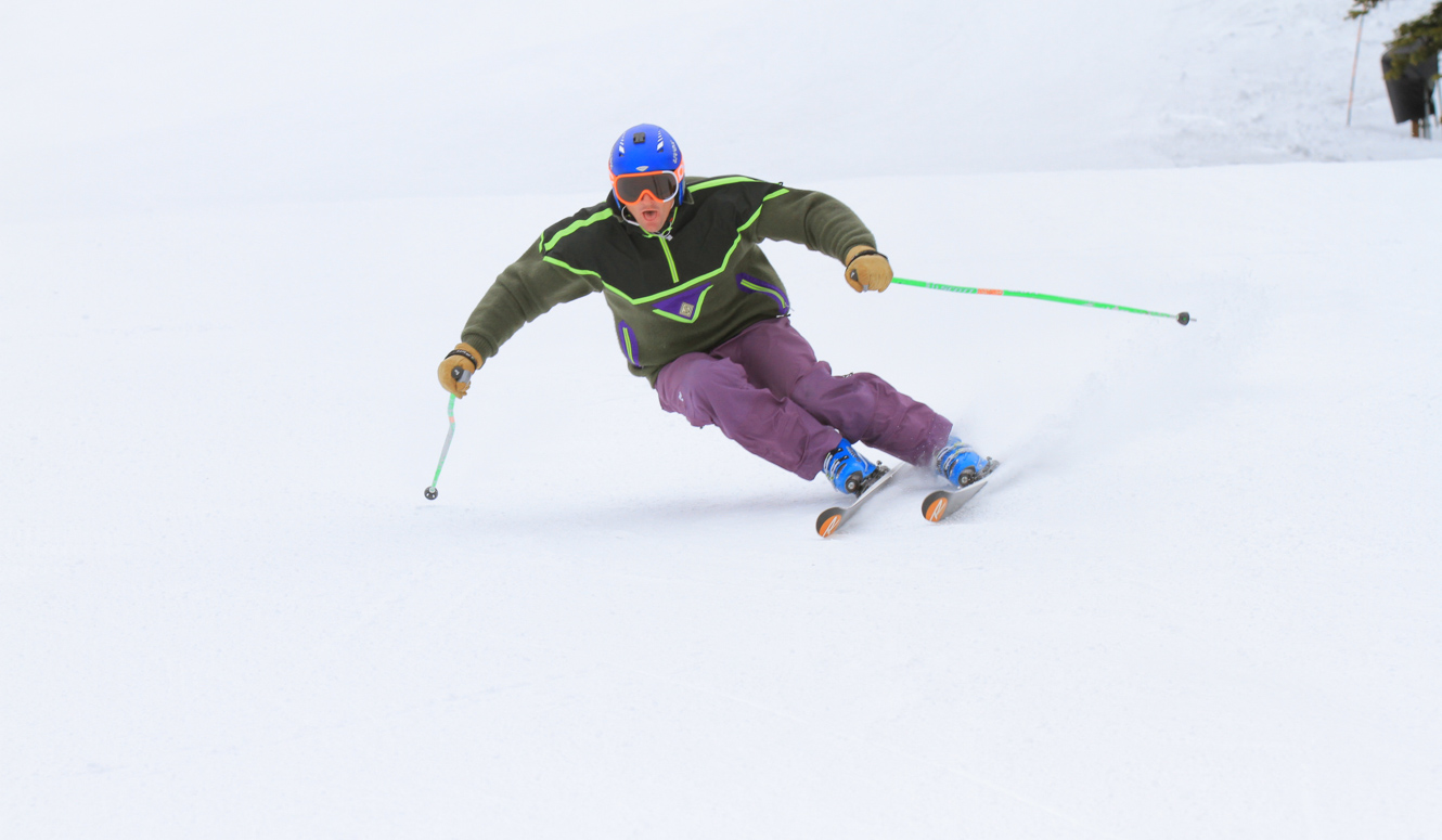Downhill skier racing down a groomed slope