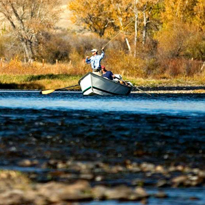 Fly fisherman in a drift boat on a river on a sunny fall day.
