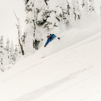Downhill skier racing through soft powder snow